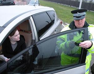 Policajt kontroluje propustnost tónovaného autoskla.